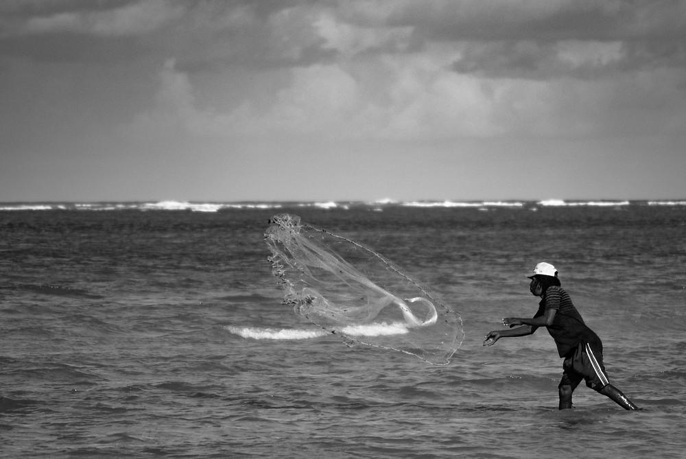Fotografía de un pescador lanzando la red