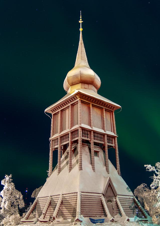 Kiruna kyrkas klocktorn med norrsken i bakgrunden.
