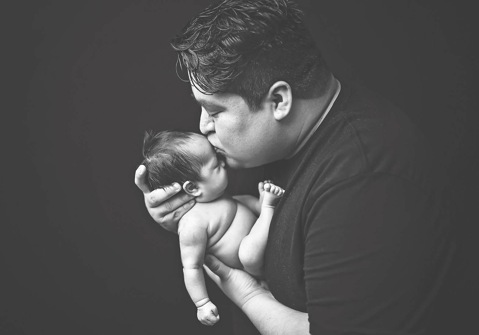 newborn in dad's hands indianapolis photo studio session black and white