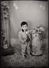 1960s black & white photograph of a child wearing a suit in a photography studio