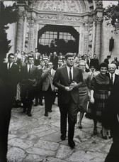 Black & white photograph of JFK exiting the Palais Élysée