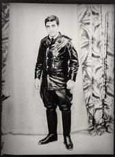 1960s black & white photograph of a man in a leather suit and riding boots in a photography studio