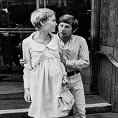 """Photograph by Hatami (1928-2017) Roman Polanski and Mia Farrow in front of The Dakota Building, New York City, on the set of """"Rosemary's Baby"""" photograph 1968 vintage gelatin silver print, signed, stamped 14.5 x 9.25 inches"""