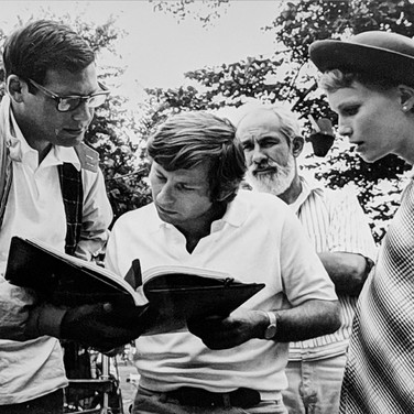 """Photograph by Hatami (1928-2017) Roman Polanski reviewing the script with Mia Farrow and William A. Fraker (director of photography) in the background, New York City, on the set of """"Rosemary's Baby"""" photograph 1968 vintage gelatin silver print, signed, stamped 8.2 x 11 inches"""