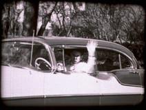 Film still of a man waving from his car
