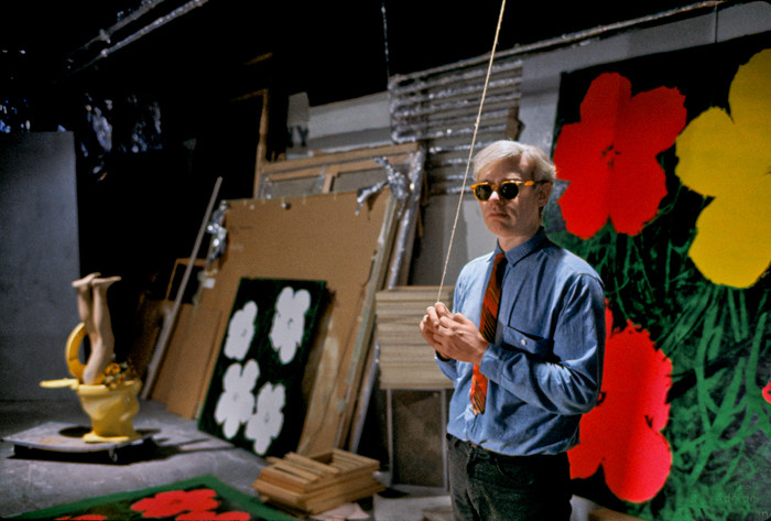 BOB ADELMAN (1930-2016) Andy Warhol at the Factory with 'Flower' paintings photograph 1965 [printed later] archival pigment print, AP, signed Paper Size: 12.25 x 18.75 inches | 31.1 x 47.6 cm  Also available:  archival pigment print on Kodak paper, edition of 50, stamped by the Bob Adelman estate Paper Size: 16 x 20 inches | 40.6 x 50.8 cm