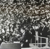 Black & white photograph of JFK smiling to a crowd during an event