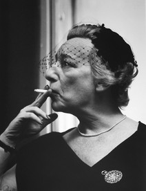Lillian Hellman smokes and poses looking left, 1952