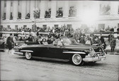 Black & white photograph of JFK and Jackie Kennedy in an official dark car