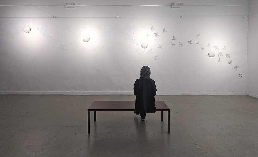 Nobuho Nagasawa sitting on bench, looking at a wall with charcoal drawings of luna moths and circular sculptures of moons