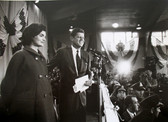Black & white photograph of JFK and Jackie in front of a crowd