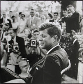 Black & white photograph of JFK profile, in the background numerous news reporters with cameras