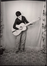 1960s black & white photograph of a child with a guitar, in a photography studio