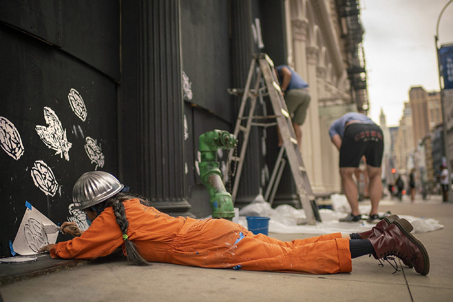 Artist wearing orange overalls and hard hat stenciling a white cicada on plywood