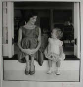 Black & white photograph of Jackie Kennedy with child sitting on steps