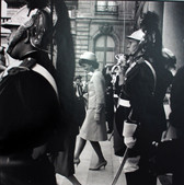 Black & white photograph of Jackie Kennedy descending stairs during a military parade