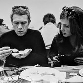 """Photograph by Hatami (1928-2017) Steve McQueen and Jacqueline Bissett conversing at lunch, on the set of """"Bullitt"""" photograph 1968 vintage gelatin silver print, signed, stamped 8.5 x 11.5 inches"""