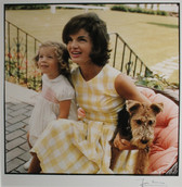 Color photograph of Jackie Kennedy in checkered white and yellow dress, with child and Airedale terrier