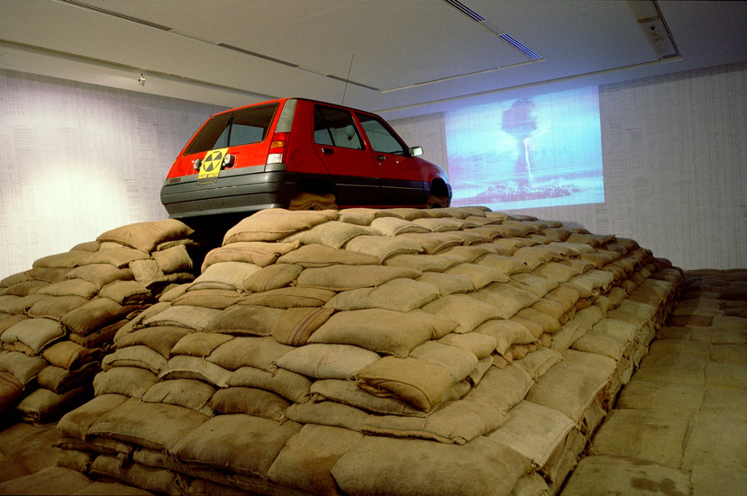 """NOBUHO NAGASAWA May 13th 1996, 10 A.M. I Called the Pentagon (1996) automobile (Renault 5), Geiger counter, jute bags, sand, barbed wire, steel, video projector, binoculars, announced nuclear tests data from the United States, England, China, France and the Soviet Union  Installation from """"Between Earth and the Heavens: Aspects of Contemporary Japanese Art II"""" at Nagoya City Art Museum, Nagoya, Japan, 1996."""