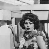 """Photograph by Hatami (1928-2017) Sophia Loren with flowers on the set of """"A Countess from Hong Kong,"""" Pinewood Studios, Buckinghamshire photograph 1966 vintage gelatin silver print 14.5 x 9.5 inches"""