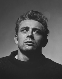James Dean poses in a torn sweater in New York City while staring up and to the right