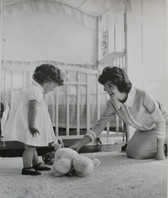 Black & white photograph of Jackie Kennedy with child in nursery