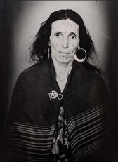 1960s black & white portrait of Amazigh woman with facial tattoos, wearing a mantle, in a photography studio