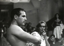 Paul Newman seated shirtless amongst crowd at the Actors Studio, 1955