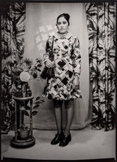 1960s black & white photograph of a young woman wearing a patterned dress and shoulder bag, in a photography studio