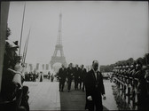 Black & white photograph of JFK walking a red carpet with Tour Eifel in the background