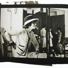 Douglas Kirkland  Mlle Chanel in the Atelier, rue Cambon. In the background is fitter Jean, working with a model. photograph 1962 [printed later]  platinum / palladium print, edition of 12, signed and numbered paper size > 16 x 20 inches