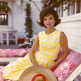 Color photograph of Jackie Kennedy in a checkered white and yellow dress sitting on a lawn chair