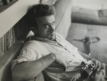 James Dean poses next to bookcase with camera while slouching on a couch in a New York City apartment