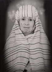1960s black & white portrait of Amazigh woman with facial tattoos, wearing a head scarf, in a photography studio