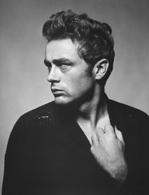 James Dean poses in a torn sweater while stretching the neckline downward with one hand in New York City