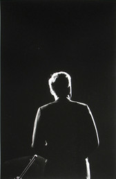 Black & white photograph of JFK from the back, lit to create a silhouette outline