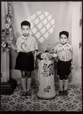 1960s black & white photograph of two children in school uniforms, in a photography studio