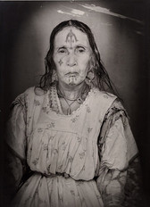 1960s black & white portrait of Amazigh woman with facial tattoos, wearing a dress, in a photography studio