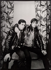 1960s black & white photograph of two men wearing leather jackets, in a photography studio