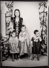 1960s black & white photograph of a mother with three children, in a photography studio