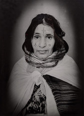 1960s black & white portrait of Amazigh woman with facial tattoos, wearing a scarf, in a photography studio