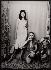 1960s black & white photograph of two women, one crouching, one standing, in a photography studio