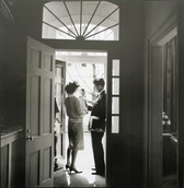 Black & white photograph of JFK and Jackie Kennedy in a doorway with a child