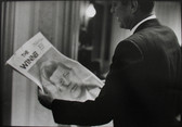 Black & white photograph of JFK reading a newspaper declaring him the winner of the election