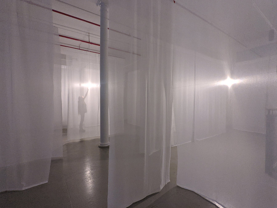 Gallery interior with translucent white scrims, figure visible though a scrim