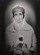 1960s black & white portrait of Amazigh woman with facial tattoos, wearing a head covering, in a photography studio