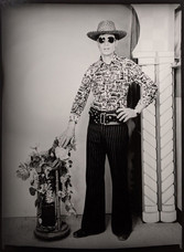1960s black & white photograph of man wearing a cowboy outfit and hat, in a photography studio