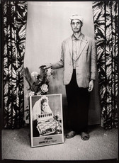 1960s black & white photograph of a man wearing a headscarf with a poster, in a photography studio