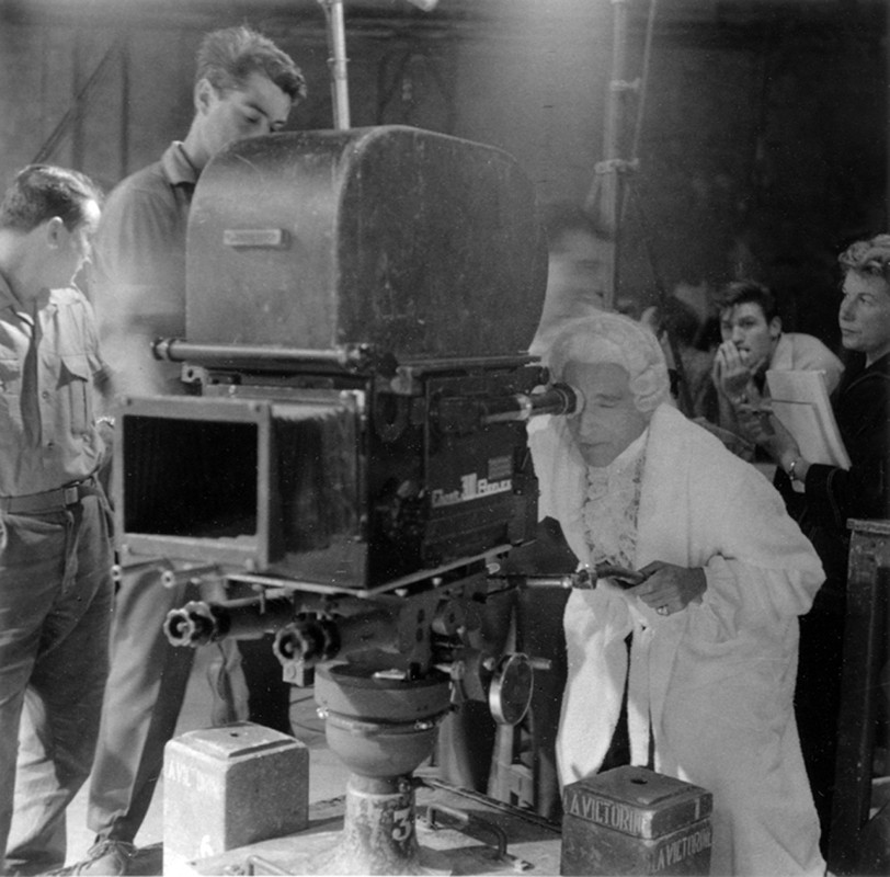 Lucien Clergue [1934-2014] Jean Cocteau in Louis XV costume operating the camera on the set of Testament of Orpheus, Nice, Les Baux de Provence photo 1959 [printed 2001] gelatin silver print, edition of 30 PF, signed Paper Size: 11.25 x 15.5 inches   28.6 x 39.4 cm Image Size: 9.75 x 9.75 inches   24.8 x 24.8 cm