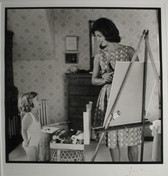 Black & white photograph of Jackie Kennedy painting at an easel, speaking to a child